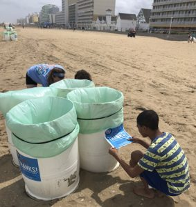 Students placing stickers on trash cans at the Virginia Beach Oceanfront.